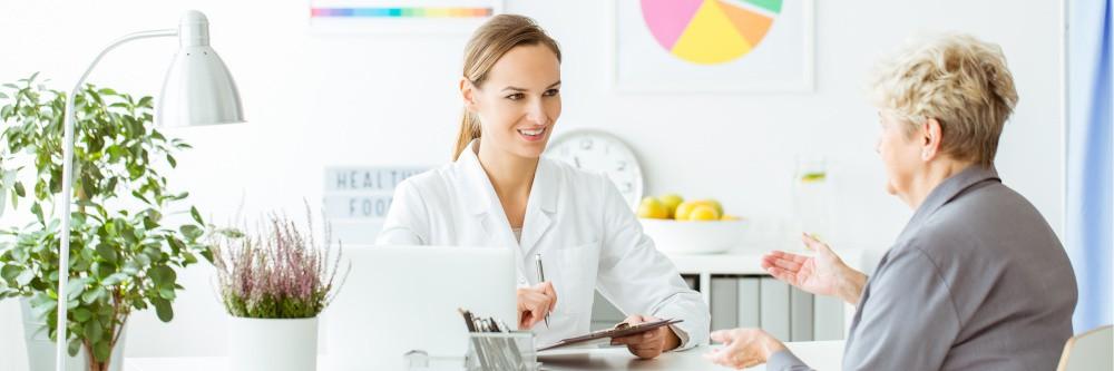 kobieta siedzaca przy biurku jest ona lekarzem dietetykiem